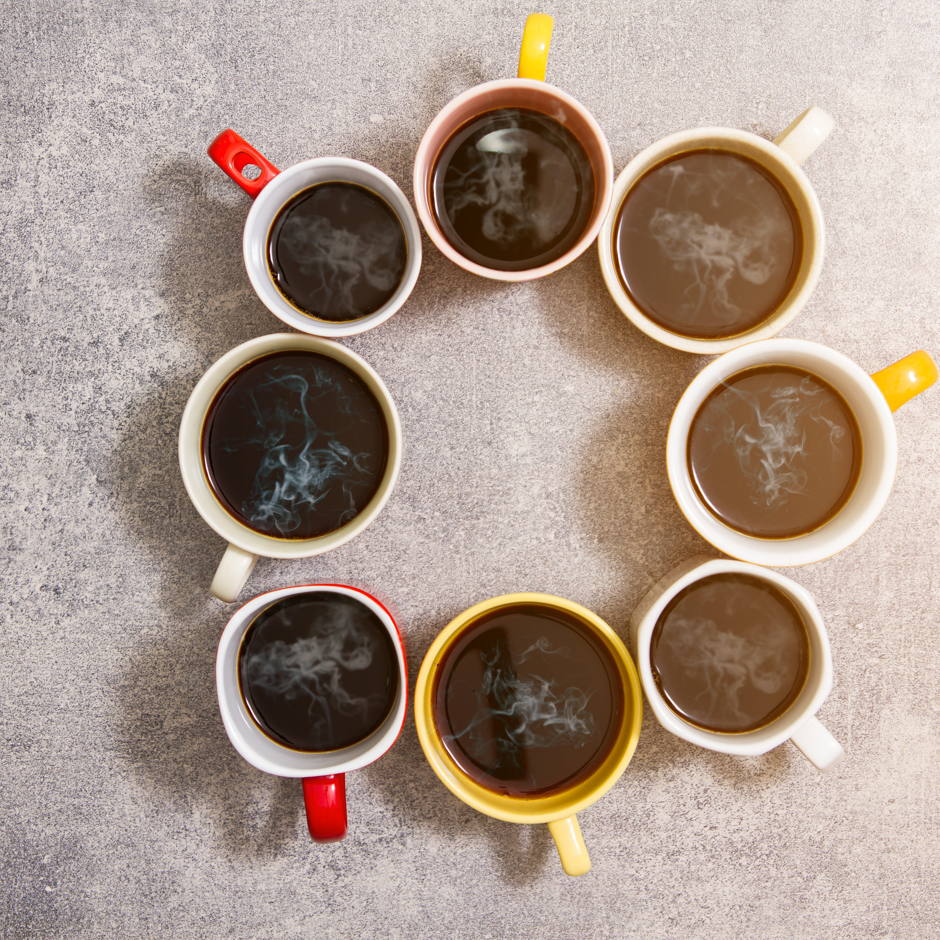 colorful cups of coffee on concrete background,top view